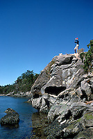 A Hiker on the Rocky Coastline of Winter Cove Provincial Park on Saturna Island, in the Southern Gulf Islands, British Columbia, Canada