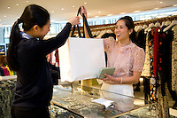 HONG KONG - MAY 04: Patricia Szeto buys in a fashion store in Landmark shopping mall in Central business district, on May 4, in Hong Kong. (Photo by Lucas Schifres/Pictobank)