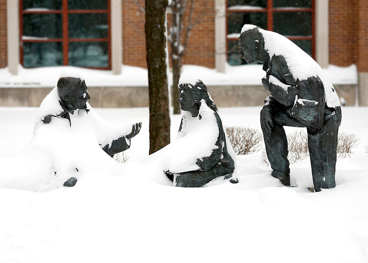 Snow coats the St. Vincent's Circle statue on the Lincoln Park campus during the New Year's snow of 2014. The statue, featuring St, Vincent de Paul talking with two students, is located just to the east of the Quad between the Richardson Library and the Schmitt Academic Center. (Photo by Jamie Moncrief)