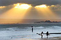 BNPS.co.uk (01202 558833)<br /> Pic: ZacharyCulpin/BNPS<br /> <br /> Pictured: Surfers walk in from the sea as a spectacular sunset breaks through the clouds.<br /> <br /> Strong coastal winds brought huge waves to Bournemouth beach last night. Surfers braved the cold weather and made most of the conditions at Bournemouth Pier.