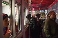 Alfred Ababio (in gray flannel scarf), of Boston, places an order at the outside take-out window at Tasty Burger on Boylston Street in the Fenway neighborhood of Boston, Massachusetts, USA, in the early hours of Saturday, Dec. 5, 2015.