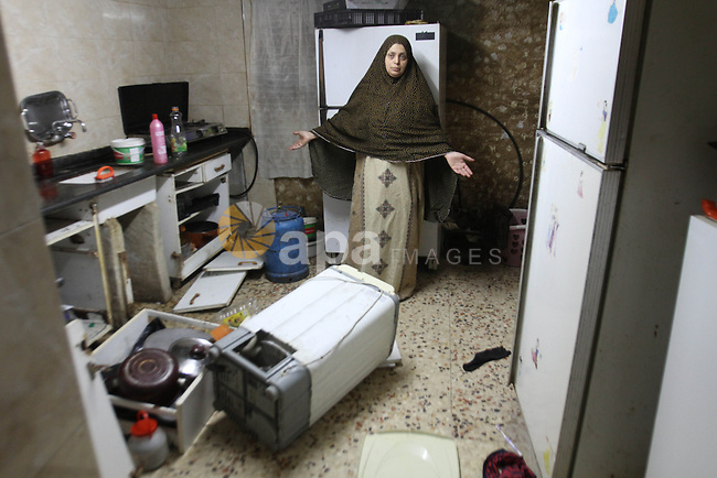 A Palestinian inspects the damage after her house was searched by Israeli forces in Al Ein refugee camp, near the West Bank city of Nablus, on June 19, 2014. as Israeli forces broadened the search for three teenagers believed kidnapped by militants and imposed a tight closure of the town. Israeli Prime Minister Benjamin Netanyahu demanded Palestinian president Mahmud Abbas's help in securing the release of three kidnapped teenagers, as the army launched a massive crackdown on Islamist movement Hamas. Photo by Nedal Eshtayah