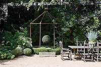 A stone faux-bois dining table from France and an iron gazebo are surrounded by waves of clipped box, magnolia and hydrangea which conceal the neighbouring building