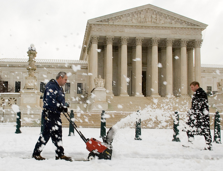 A worker with the Architect of the Capitol office uses a snow blower to clear the sidewalk in front of the Supreme Court as a predestrian walks by on Wednesday morning, Feb. 14, 2007, following a winter storm that covered the Washington area with snow and ice.