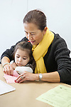 Woman teacher helping young child with an art project