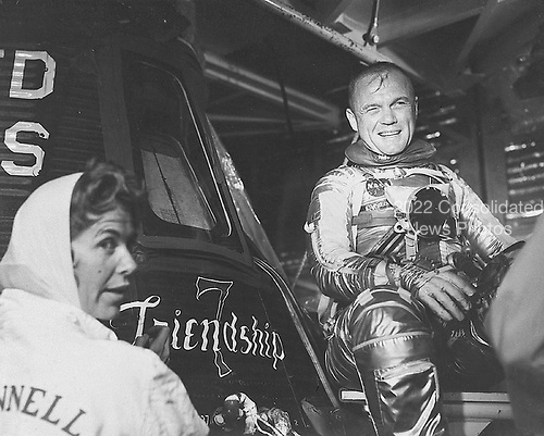 """Astronaut John H. Glenn Jr., pilot of the Mercury-Atlas 6 """"Friendship 7"""" mission, is suited up and seated beside his capsule during pre-flight activity at Cape Canaveral. Glenn is shown with artist Cecilia Bibby who painted the name """"Friendship 7"""" on his Mercury spacecraft..Credit: NASA via CNP"""