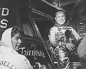 "Astronaut John H. Glenn Jr., pilot of the Mercury-Atlas 6 ""Friendship 7"" mission, is suited up and seated beside his capsule during pre-flight activity at Cape Canaveral. Glenn is shown with artist Cecilia Bibby who painted the name ""Friendship 7"" on his Mercury spacecraft..Credit: NASA via CNP"