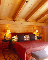 The reds and browns of the soft furnishings add to the warmth of the wood-clad bedroom