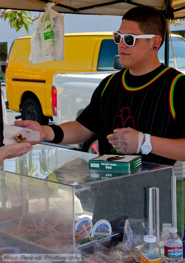 Gilbert hands out a sample of vegan pesto on spinach-filled flatbread to a customer.  SR.