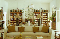 One end of the large living room functions as a library and is lined with bookshelves which also display a collection of antique spice canisters