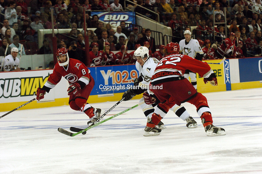 The Pittsburgh Penguins' Sidney Crosby tries to retain control of the puck despite the efforts of the Carolina Hurricanes' Matt Cullen (8) and Mike Commodore (22) in Raleigh, NC Friday, February 10, 2006. The Penguins won the game 4-3...