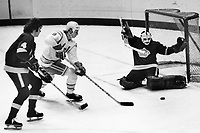 Seals vs Los Angeles Kings, Seals Larry Patey shot on goalie Rogie Vachon and #4 Dave Hutchison. (1975 photo/Ron Riesterer)
