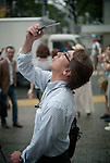 Tokyo, Japan - 22nd of July 2009 - A japanese man taking a picture of the partial solar eclipse (75%) with his mobile phone.