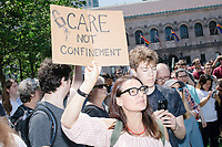 """A person holds a sign reading """"Care not confinement"""" as Wayfair employees demonstrate in Copley Square to protest their company's sale of furniture to detainment camps for children operated by US Customs & Border Protection (CBP) on the Mexico border in Boston, Massachusetts, USA, on Wed., June 26, 2019. Wayfair is an online furniture retailer. Employees are asking for the company to set ethics standards for sales.  The Wayfair employees were joined by union representatives, PRIDE activists, and other groups in solidarity.  This action occurred the week after US government legal representatives argued that children held in CBP facilities did not need soap or beds to meet the """"safe and sanitary"""" standard of care required by law after months and years of criticism of Trump administration policies of family separation and cruel treatment of those held at its facilities."""