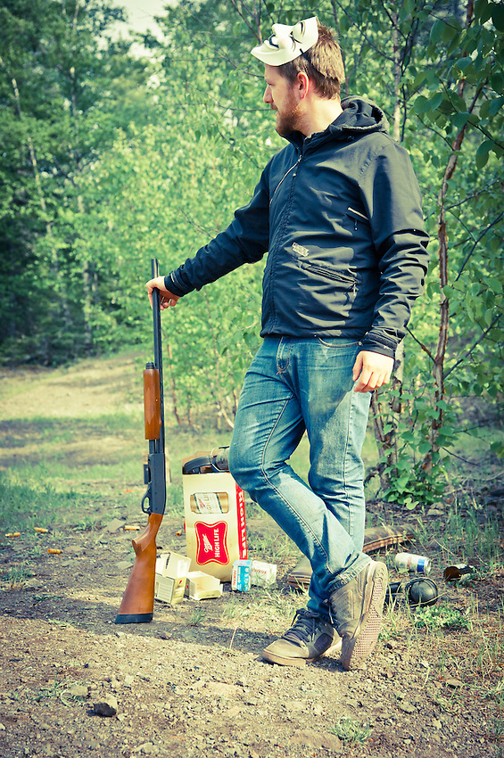 Filmmaker Aaron LaRocque poses with a shotgun while visiting Copper Harbor Michigan to make a mountain biking film.