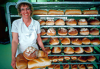 Woman holding tray of fresh-baked bread in bakery