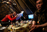 Two Nenets women read a newspaper while seated with a man at a table inside their choom (tent) in Naryan-Mar. Outside it is -40 Celcius. /Felix Features