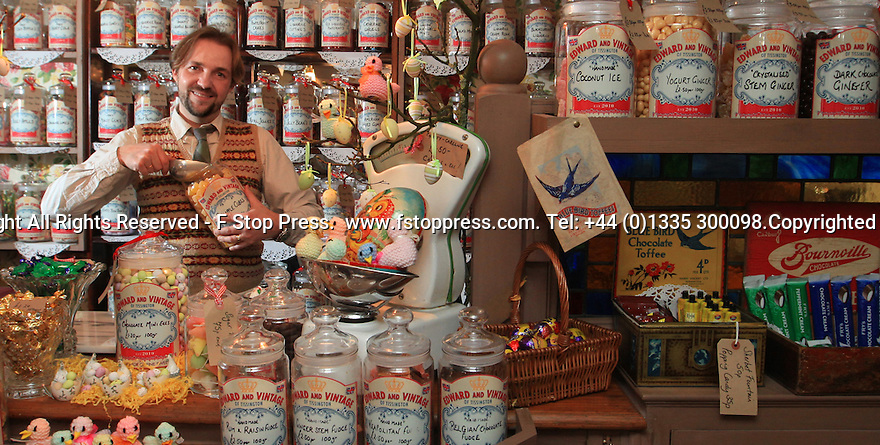 Picture dated 06/03/13 shows David Westcott-Walker (40) behind the counter of his traditional sweet shop, Edward and Vintage, Tissington, Derbyshire.....Full Copy here:  http://www.fstoppress.com/articles/vintage-sweet-shop/.....The future is looking more than just a little sweet for a vintage sweet shop owner who is in the running to become Britain's Best Vintage Shop of the Year......The tiny shop is like a museum exhibiting confectionery from a bygone era. Walking in to Edward and Vintage in the village of Tissington, Derbyshire is like stepping out of a time machine that has traveled back sixty years....The shelves are stacked from floor to ceiling with glass jars full of sweets. Each jar has a handwritten label and every name ignites another childhood memory; Pear Drops, Rosy Apples, Lions Wine Gums and Sherbert Lemons are just a few of more than 350 different chunks of nostalgia being sold by the bag....It's not only the sweets, fudge and chocolates that are old fashioned. Everything in the shop helps to keep you believing you're in the 1940s - from an old wireless that plays Glen Miller, to the 1920s shop telephone and the antique till that still rings up the prices in old money....All Rights Reserved - F Stop Press.  www.fstoppress.com. Tel: +44 (0)1335 300098.