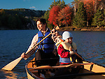 Father and his 3 year old son paddling a canoe. Fall nature scenic, Killarney Provincial Park, Ontario, Canada.