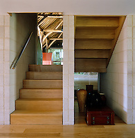 The smooth wood of the double-flight staircase contrasts with the texture of the exposed brick of the stairwell