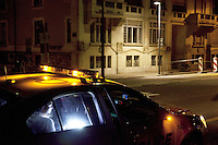 "Switzerland. Geneva. A convict man seats in a police car on duty, parked on the Quai du Mont-Blanc, during the night. The inmate is a Gypsy man from France. The Romani people are also known by a variety of other names, in English as Gypsies and Roma, in Central and Eastern Europe as Tsigani. French Romani people are generally known in spoken French as ""Manouches"" or ""Tsiganes"". ""Romanichels"" or ""Gitans"" are considered pejorative and ""Bohémiens"" is outdated. 1.04.12 © 2012 Didier Ruef"