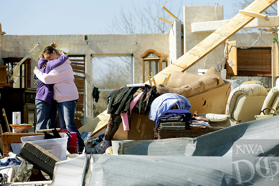 Maria Cook, left, and Barbara Giles hug in what is left of Cook's home at River Oaks mobile home community after the first batch of severe weather in this year's tornado season devastated the mobile home park, Thursday, March 26, 2015, in Tulsa, Okla. Giles lives nearby and suffered extensive damage as well. (AP Photo/Tulsa World, Mike Simons)  KOTV OUT; KJRH OUT; KTUL OUT; KOKI OUT; KQCW OUT; KDOR OUT; TULSA OUT