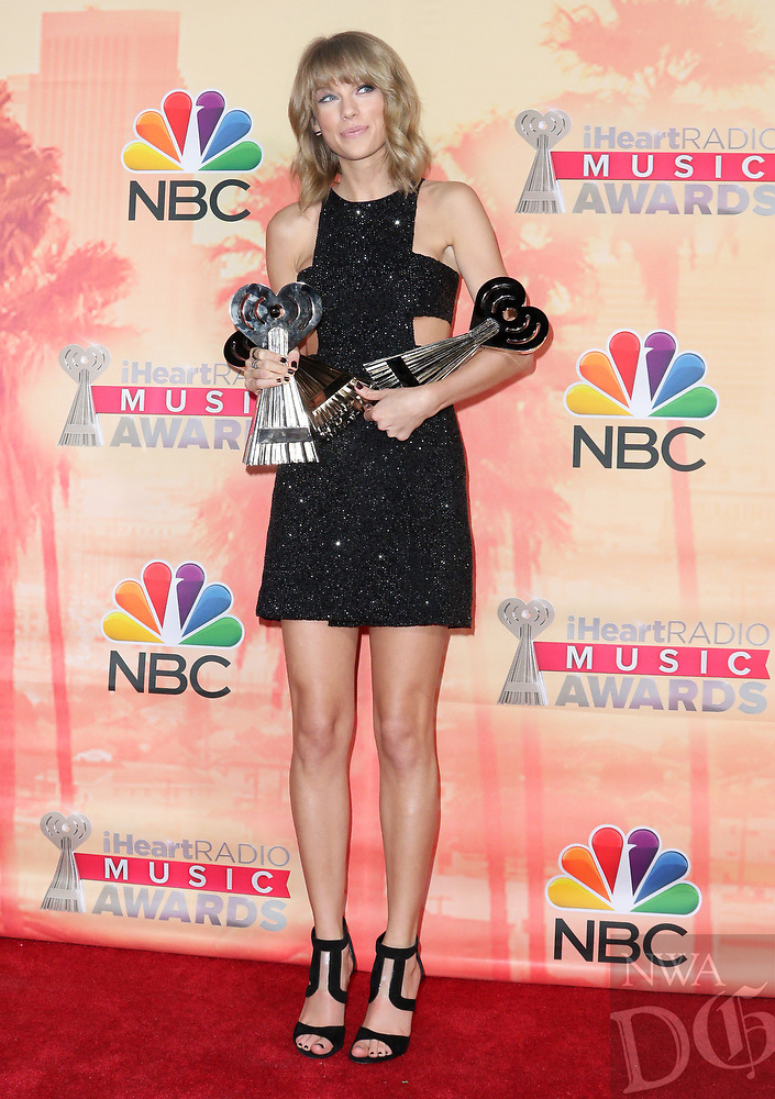 Taylor Swift poses in the press room with the awards for best lyrics for ìBlank Spaceî, song of the year for ìShake It Offî and artist of the year at the iHeartRadio Music Awards at The Shrine Auditorium on Sunday, March 29, 2015, in Los Angeles. (Photo by John Salangsang/Invision/AP)