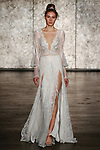 Model walks runway in a V front & back embroidered lace gown with long sleeves and double front slits, from Inbal Dror Fall 2018 bridal collection on October 5, 2017; during New York Bridal Fashion Week.