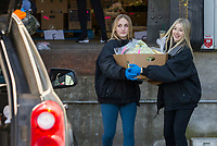 Lily Grace Hassebrock (left), 13, of Springdale and Brooklyn Thompson, 14, of Bentonville volunteer to help carry orders to cars Saturday, March 21, 2020, at Kimball and Thompson Produce in Lowell. The business supplies fresh produce to the food service industry, including public schools, restaurants and hotels. With many of their usual clients closed due to the covid-19 pandemic, owner Chris Thompson (Brooklyn's father) says they are adapting to get their inventory directly to consumers who need it at wholesale prices. Thompson says he is also reaching out to the Northwest Arkansas Food Bank to make sure nothing goes to waste. <br /> <br /> The business began selling to the public Friday morning, and many shelves were already bare Saturday. Thompson says they will be working to keep their inventory updated as they navigate the temporary change to their business model. <br /> <br /> Staff and family members are pitching in to help fill orders curbside while minimizing personal contact and practicing strict sanitizing measures. Customers are asked to place orders ahead of time by calling 479-872-0200 or emailing orders@ktproduce.com. Pickup times are Monday through Saturday from 9 a.m. to 4 p.m., and Sunday from 11 a.m. to 2 p.m. at 305 S. Lincoln St. in Lowell. <br /> <br /> Check out nwaonline.com/200322Daily/ for today's photo gallery.<br /> (NWA Democrat-Gazette/Ben Goff)