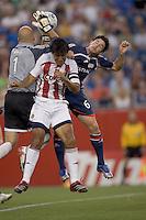 Matt Reis grabs the ball as Claudio Suarez (Chivas USA, striped) and Jay Heaps (Revolution, blue) crash the net. New England Revolution tied Chivas USA, 1-1, at Gillette Stadium on July 7, 2007.