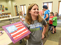 """NWA Democrat-Gazette/FLIP PUTTHOFF <br /> SALUTE TO THE FLAG<br /> Hayley Shrum, 11, shows an Ameican Flag she painted on Wednesday July 3 2019 at the Bentonville Public Library. The art project was part of the """"Salute to the Flag"""" activity for children. Kids learned about the first lunar landing and painted a flag similar to the flag astronauts unfurled on the moon. They heard the story """"One Giant Leap"""" in observance of the 50th anniversary of the first lunar landing that took place on July 20, 1969."""