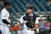 Catcher Scott Manea (25) hands the ball to Tony Dibrell (8) after the pitcher tied a Fireflies single-season strikeout record on Tuesday, August 28, 2018, at Spirit Communications Park in Columbia, South Carolina. Dibrell went on to break the record at 138. (Tom Priddy/Four Seam Images)