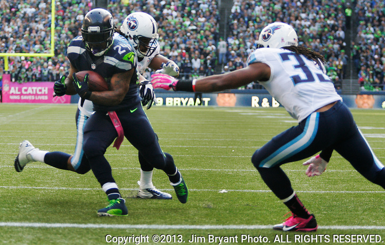 Seattle Seahawks running back Marshawn Lynch , center, leaps into the end zone and scores his second touchdown of the game on a 3-yard run against the Tennessee Titans in the fourth quarter at CenturyLink Field in Seattle, Washington on  October13, 2013. Watching Lynch are Titans safety's Bernard Pollard (31) and MIchael Griffin. Lynch scored two touchdowns and rushed for 77 yards and caught five passes for 78 yards in the Seahawks 20-13 win over the Titians.    ©2013. Jim Bryant Photo. All Rights Reserved.