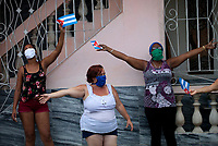 HAVANA, CUBA - May 01: Cubans women celebrate May Day outside of their house on May 01, 2020 in Havana, Cuba. The Cuban government suspended the celebration of May Day one of the largest annual march and calls to the citizens to stay home (Photo by Eliana Aponte/VIEWpress)