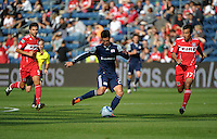 New England midfielder Benny Feilhaber (22) passes the ball in between Chicago midfielders Baggio Husidic (9) and Pavel Pardo (17).  The Chicago Fire defeated the New England Revolution 3-2 at Toyota Park in Bridgeview, IL on Sept. 25, 2011.