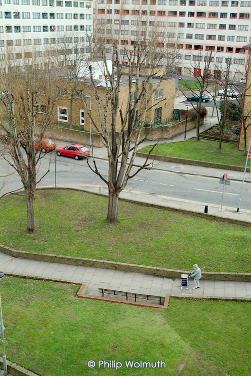An elderly woman pushes a shopping trolley across an open space on Lisson Green Estate, City of Westminster, London.