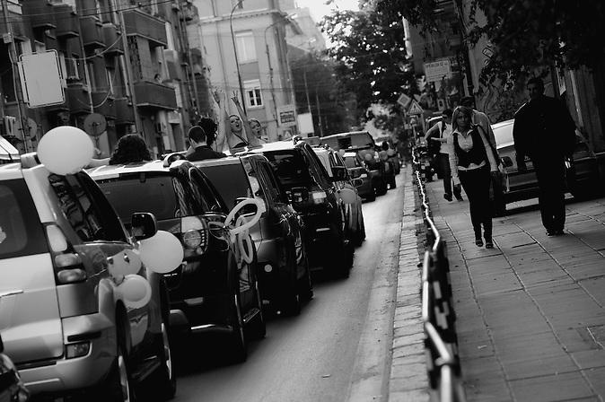 Abiturientinnen schreien aus dem Auto, während sie in einem Stau in der Innenstadt von Sofia, Bulgarien, stehen. Abschlussfeiern von Abiturienten in Bulgarien. / Girls are shouting out of the car in the traffic jam in the downtown of Sofia, Bulgaria. High-School graduation parties in Bulgaria.