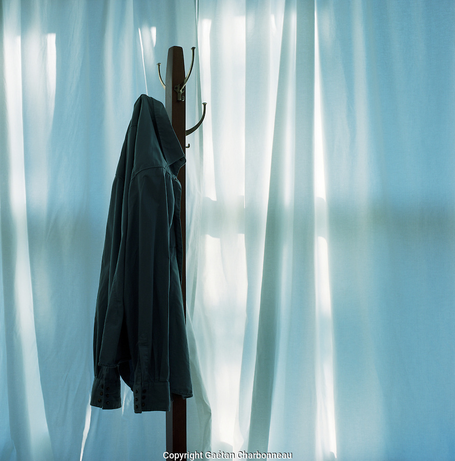 Blouse on a hook, behind a blue curtain