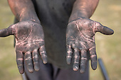 Rio Negro, Amazonas State, Brazil. The blackened hands of a charcoal worker.