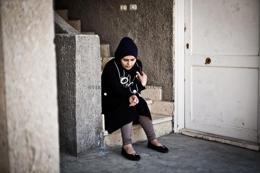 EGYPT, Cairo: Maha is listening to Kurdish music on her phone while the children are playing in front of her. Maha doesn't wish to take the boat to go to Europe, scared of what could happen during the trip. Anyway, she will follow her husband whatever is the decision. <br /> <br /> &Eacute;gypte, Le Caire: Maha est &eacute;coute de la musique kurde sur son t&eacute;l&eacute;phone pendant que les enfants jouent en face d'elle. Maha ne souhaite pas prendre le bateau pour aller en Europe, peur de ce qui pourrait arriver pendant le voyage. Quoi qu'il en soit, elle suivra son mari quelle que soit la d&eacute;cision.