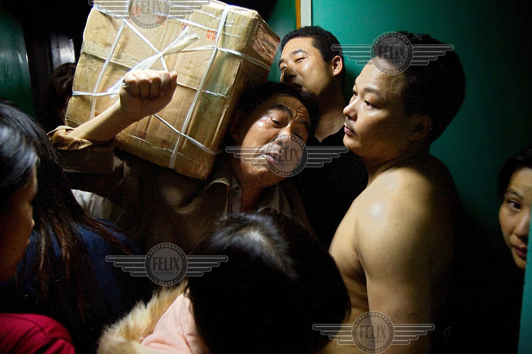 Migrant textile workers squeeze into a train on their annual holiday home during Chinese New Year.