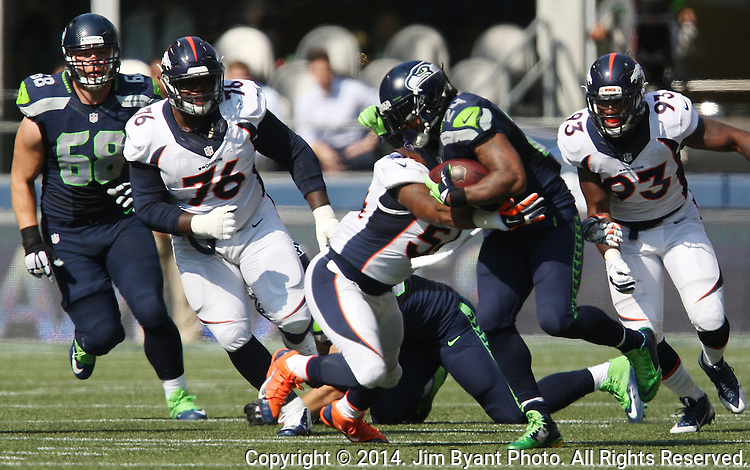 Seattle Seahawks running back Marshawn (24) is brought down by Denver Broncos linebacker Brandon Marshall (54) at CenturyLink Field in Seattle, Washington on September 21, 2014. Lynch rushed for 88 yards and scored two touchdowns in the Seahawks overtime  26-20 win against the Denver Broncos.    ©2014. Jim Bryant Photo. All rights Reserved.