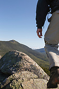 A hiker makes his way across the summit of Mount Liberty during the summer months. Located in the White Mountains, New Hampshire USA