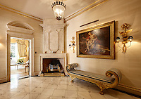 An opulent ante-room with a gilded cornice and a marble floor.  A painting hangs above an empire style seat with striped upholstery next to a corner fireplace.