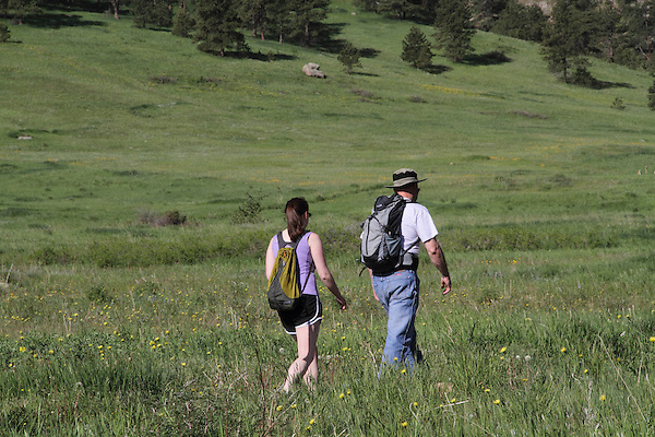 Caucasian father and daughter hiking in meadow, Chautauqua Park, Boulder, Colorado, USA .  John leads private photo tours in Boulder and throughout Colorado. Year-round.
