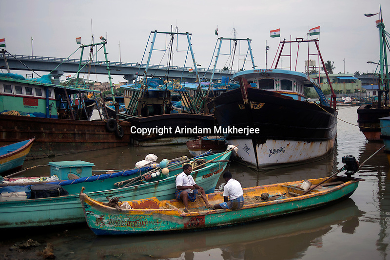 Fishermen stitching a net on a boat at Kichankuppam fishing port at Nagapattinam. This was one of the most affected areas by 2004 Tsunami in Tamil Nadu, India.