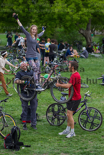 Participants lift a girl with her bike before the annual bike lifting that marks the finish of the completion of the Critical Mass their yearly tour on Earth Day around the city demonstrating the importance and popularity of bicycle as a mean of everyday city transportation in Budapest, Hungary on April 22, 2012. ATTILA VOLGYI