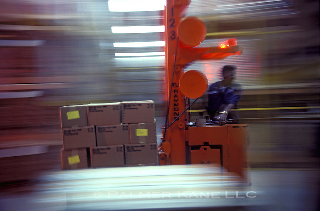 Man moving boxes on forklift, blurred background