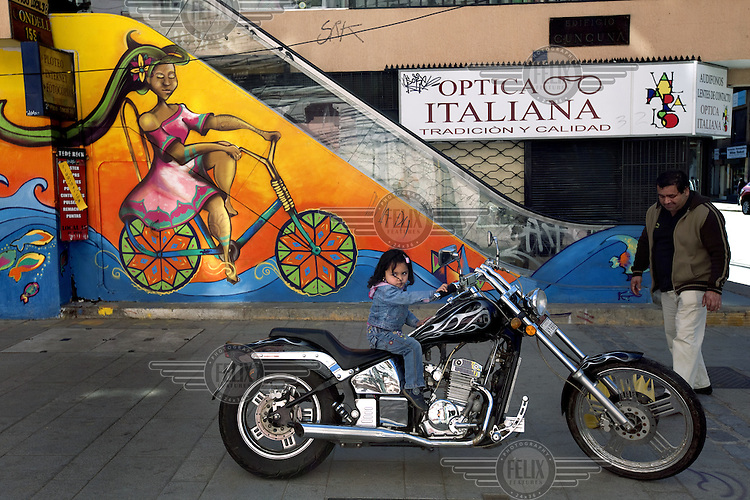 Danae Astudillo, 3, sits on a chopper motorcycle infront of a graffit piece depicting a similar scene.