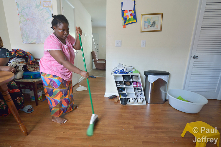 Christina Batachoka sweeps the floor of her apartment in Durham, North Carolina. A refugee from the Democratic Republic of the Congo, Batachoka was resettled in Durham by Church World Service, which resettles refugees in North Carolina and throughout the United States.<br /> <br /> <br /> Photo by Paul Jeffrey for Church World Service.